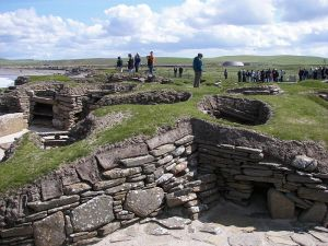 Visitors examining the remains of another sophisticated Neolithic structure in Orkney - Scara Brae.