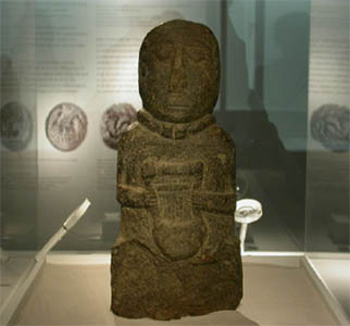 Statue of Iron Age 'bard' clutching a Celtic lyre, or 'Crwth'. The lyre was common to the Greeks from an early period.